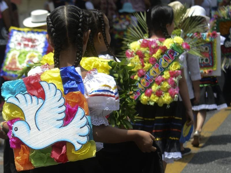 A traditional 'silleterito' participates in a parade with a 'silleta' (flower arrangement) with the theme 'peace' in Medellin. (AFP)