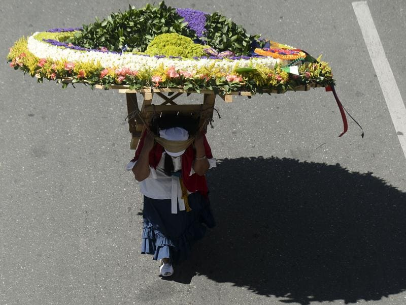 A woman carries a flower arrangement during the parade. (AFP)
