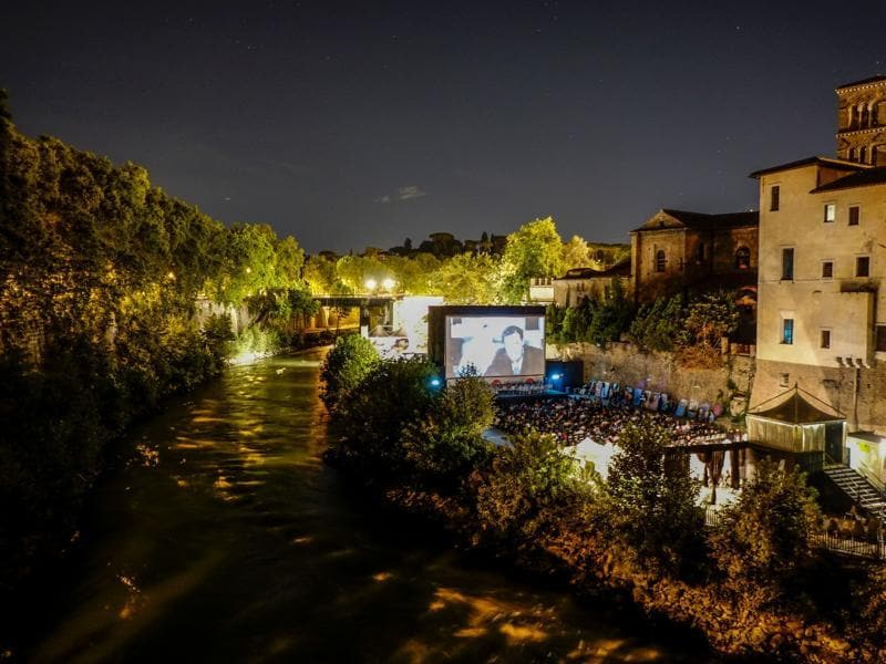 People attend a movie in an open air cinema on the Tiber Island in downtown Rome. (AFP)