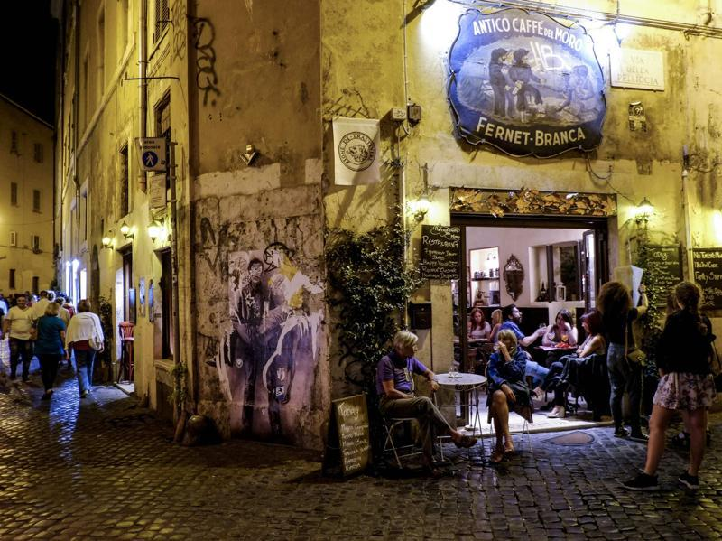 People sit outside a cafe in the district of Trastevere. The gorgeous lights and the lively atmosphere is perfect for a long walk at night. (AFP)