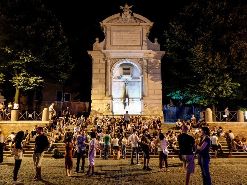 People sit on the stairs of the fountain on Piazza Trilussa (Trilussa Square) in the district of Trastevere. (AFP)