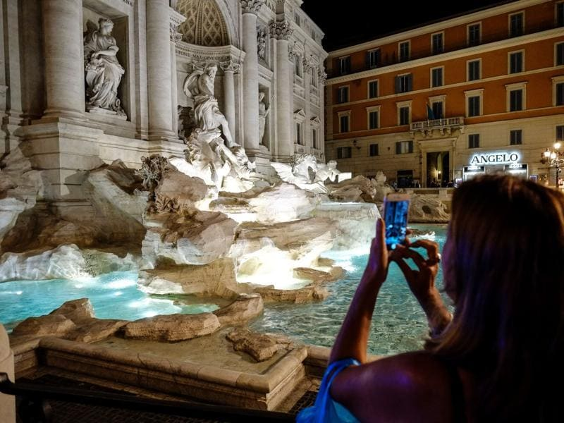 A woman takes a picture of the Trevi Fountain. (AFP)