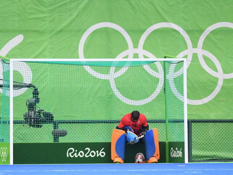 India's goalkeeper Sreejesh Parattu sits in the net after the men's field hockey Germany vs India. (AFP Photo)