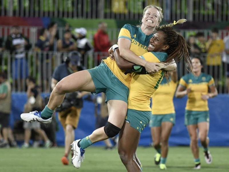 Australia's Ellia Green lifts up a teammate as they celebrate victory in the women's rugby sevens gold medal match between New Zealand and Australia. (AFP Photo)