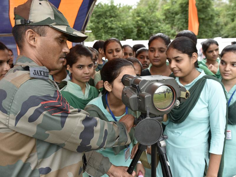 LOOK AT THAT! Army personnel showing equipment to students during an exhibition in Amritsar on Wednesday. (Gurpreet Singh/HT Photo)