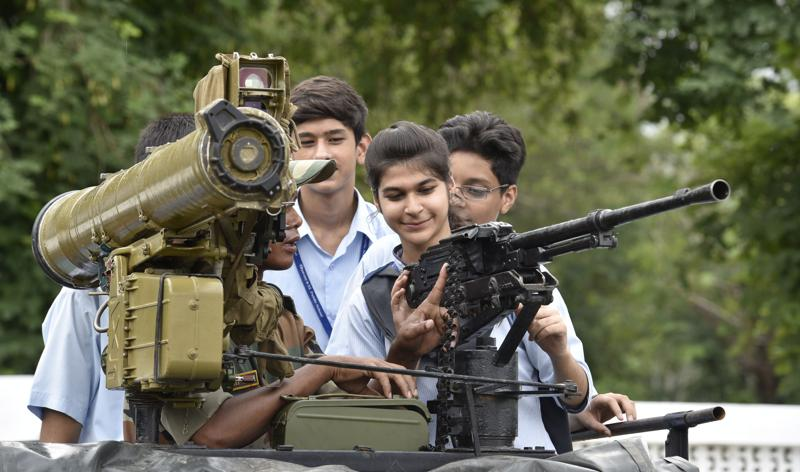 OH, SHOOT! An army personnel tells a girl about a gun at an exhibition in Amritsar on Wednesday. (Gurpreet Singh/HT Photo)