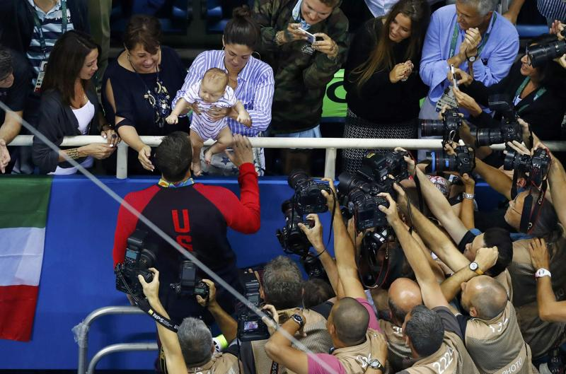 Phelps  celebrates with his son Boomer and fiancee Nicole Johnson and mother Debbie after the victory ceremony.  (REUTERS photo)