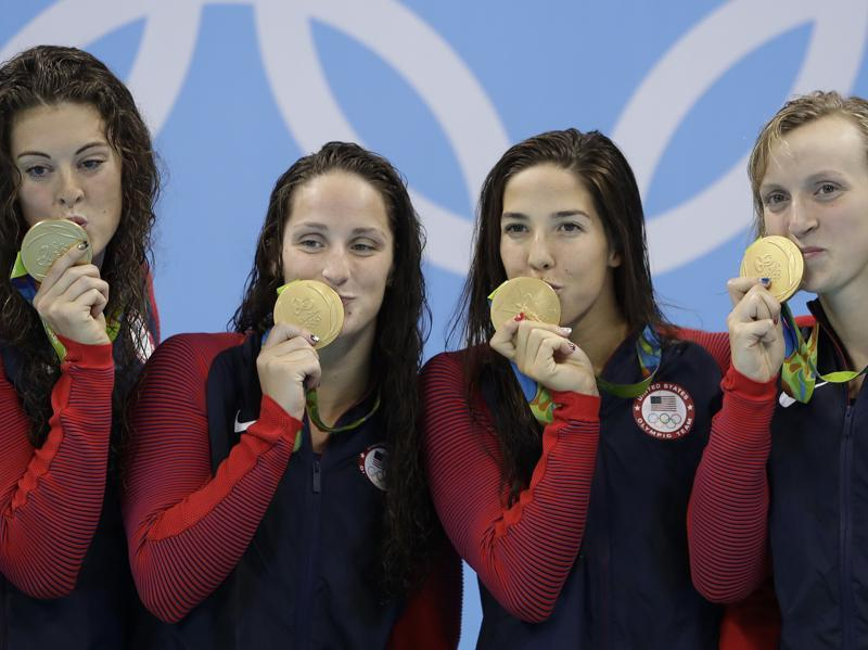 United States' Allison Schmitt, Leah Smith, Maya DiRado and Katie Ledecky, from left, kiss their medals during the women's 4 x 200-meter freestyle relay medals ceremony. (AP Photo)