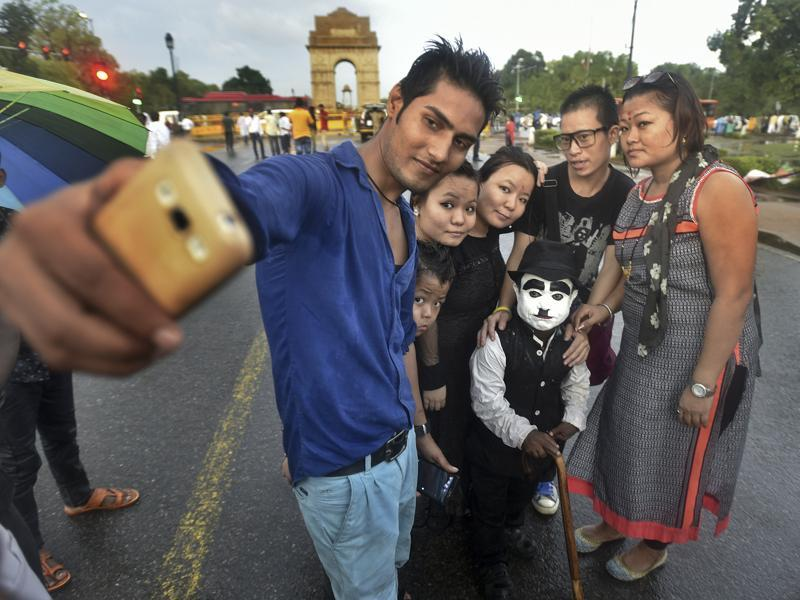 Work is seemingly simple: posing for photographs with enthusiastic tourists thronging India Gate. He charges Rs.10-20 for every selfie shot with him. Most are more than glad to pay for this unique opportunity, but there are some who don't honour their commitment, refusing to pay after getting photos clicked.  (Raj K Raj/HT PHOTO)