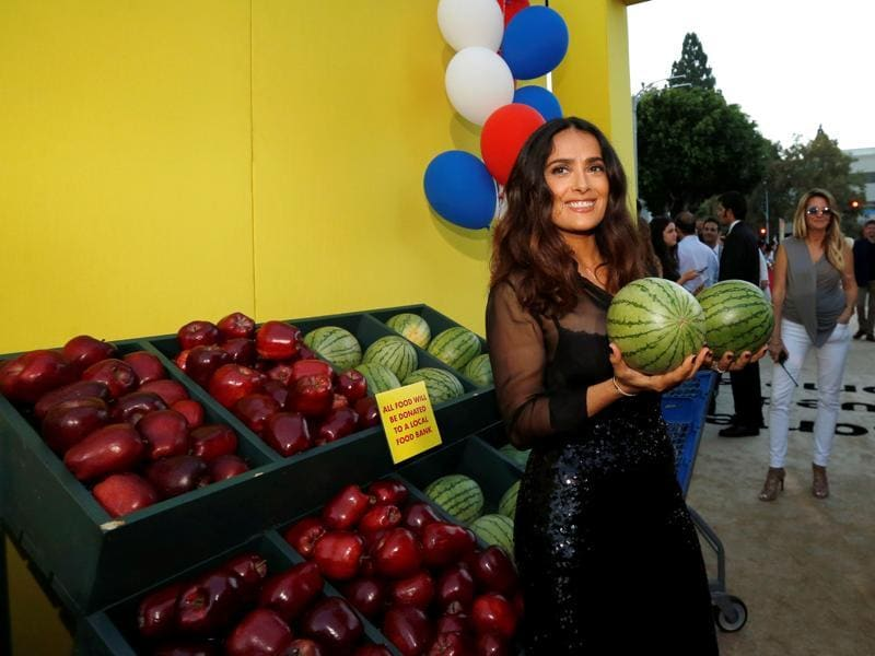 Salma Hayek holds two melons as she poses at the premiere for the movie Sausage Party. (REUTERS)