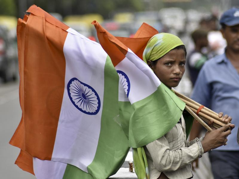 A woman sells the national flag ahead of the Independence Day celebration at Chirag Delhi. (S.Burmaula /ht photo)
