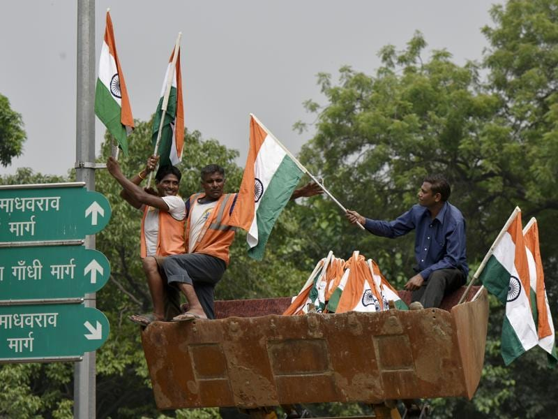 Civic body workers install tricolours on electric poles in Delhi. (Vipin Kumar/HT PHOTO)
