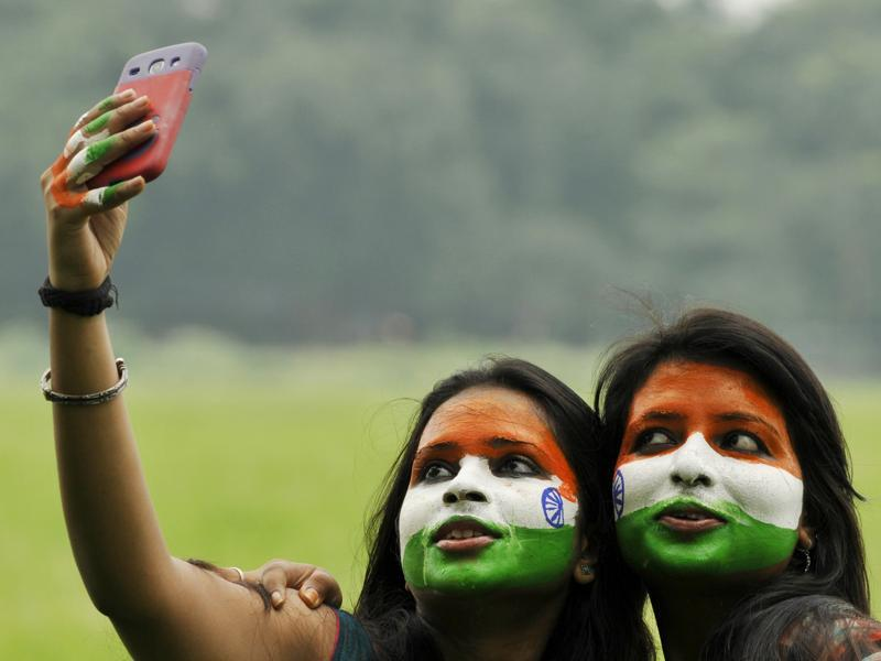 Women with faces painted in the colour of the national flag take selfies at Maidan in Kolkata. (Samir Jana/HT PHOTO)