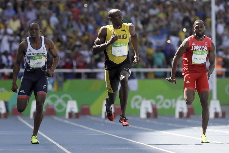 Bolt, centre, Trinidad and Tobago's Richard Thompson, right, and Britain's James Dasaolu compete in a men's 100-metre heat. (AP)