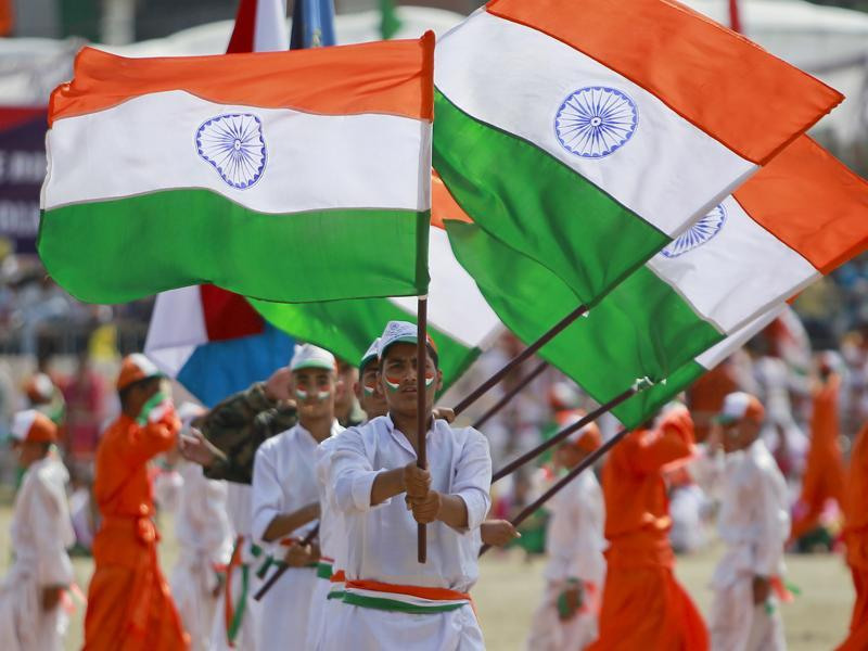 Students wave national flag as they perform during India's Independence Day celebrations, in Jammu. (AP/Channi Anand)
