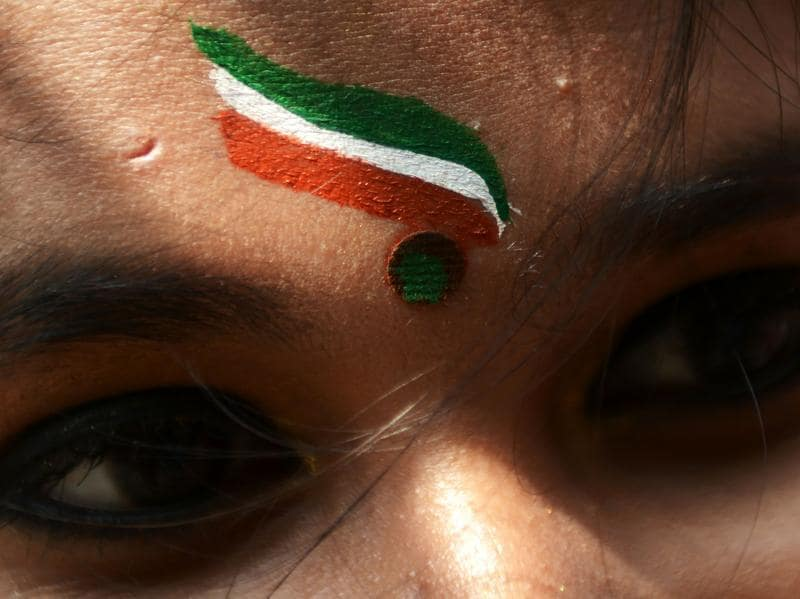 A schoolgirl wears the Indian tricolor as she prepares to participate in a cultural programme for Independence Day celebrations at a school in Kolkata. (AFP/Dibyangshu SARKAR)