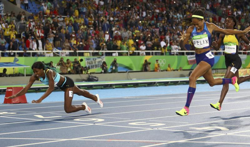 While most sprinters choose to leap forward at the end, neck forward, Miller took a different approach. While approaching the finish,  she was neck and neck with Allyson Felix (right). Perhaps realising she may have to settle for silver, Miller launched herself forward. (REUTERS)