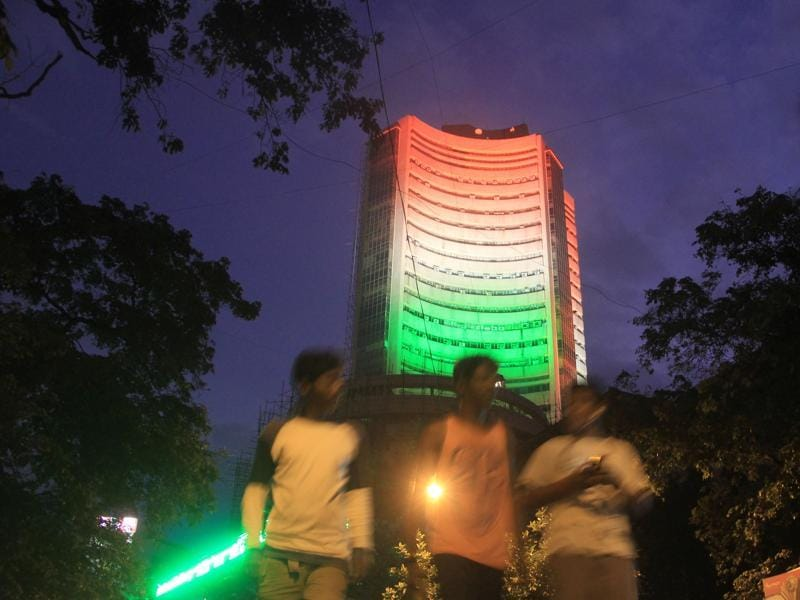 People walk past the lit-up BSE building. (BHUSHAN KOYANDE)