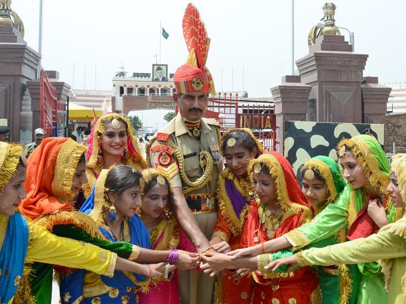Giddha girls tying Rakhis on the wrists of Border Security Force ( BSF) Jawans on the eve of Raksha Bandhan festival at Attari-Wagha Border in Amritsar. (Gurpreet singh/ht photo)