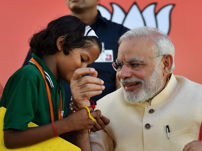 A school girl ties Rakhi to Prime Minister Narendra Modi on the occasion of Rakha Bandhan.  (PTI)
