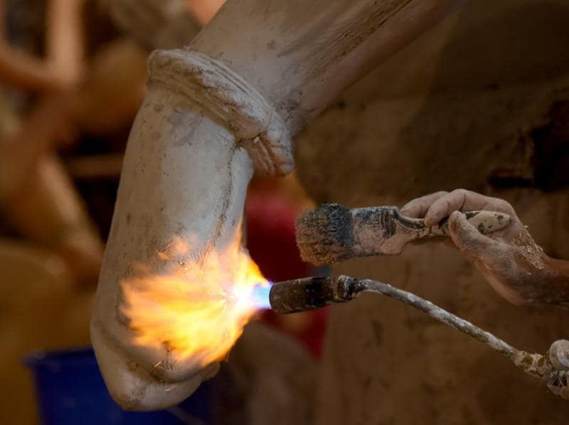 Fire for Festivities: A sculptor uses a flame torch and a brush for an idol at a city workshop on Tuesday.  (Pratik Chorge)