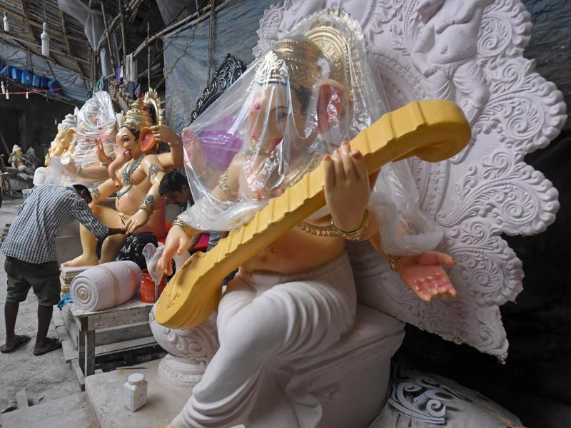 Under Cover: A Ganesha idol is covered with a plastic sheet as an artist devotes himself to monitor other idols at workshop in Mumbai n Tuesday. (Pratik Chorge)