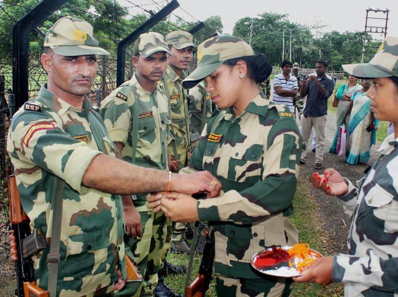Women constables of the Border Security Force (BSF) tie rakhi to their male colleagues during the celebrations of Raksha Bandhan festival at the India-Bangladesh Border near Balurghat in South Dinajpur district of West Bengal.  (PTI)
