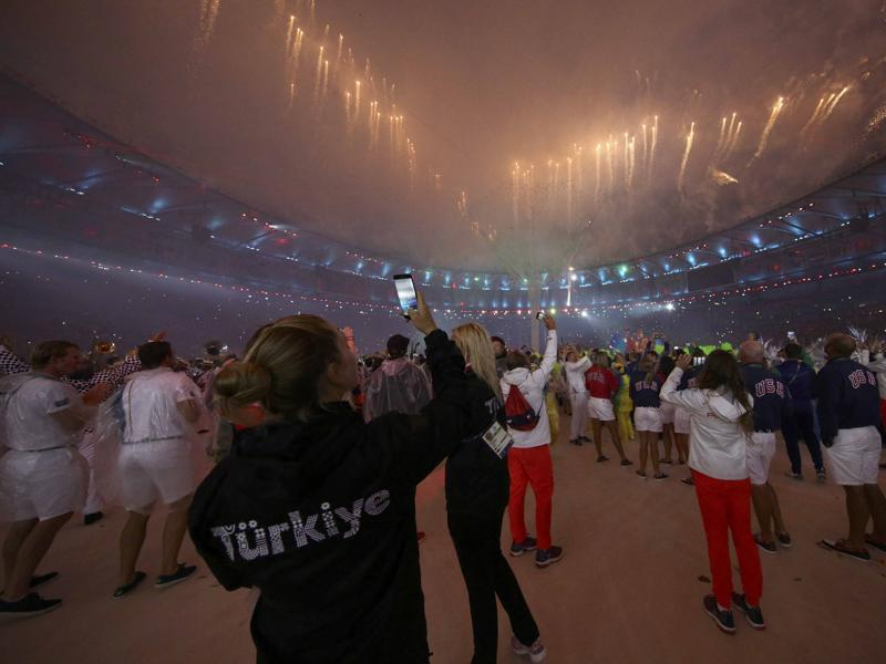 Athletes of various countries take photographs of the fireworks. (REUTERS)
