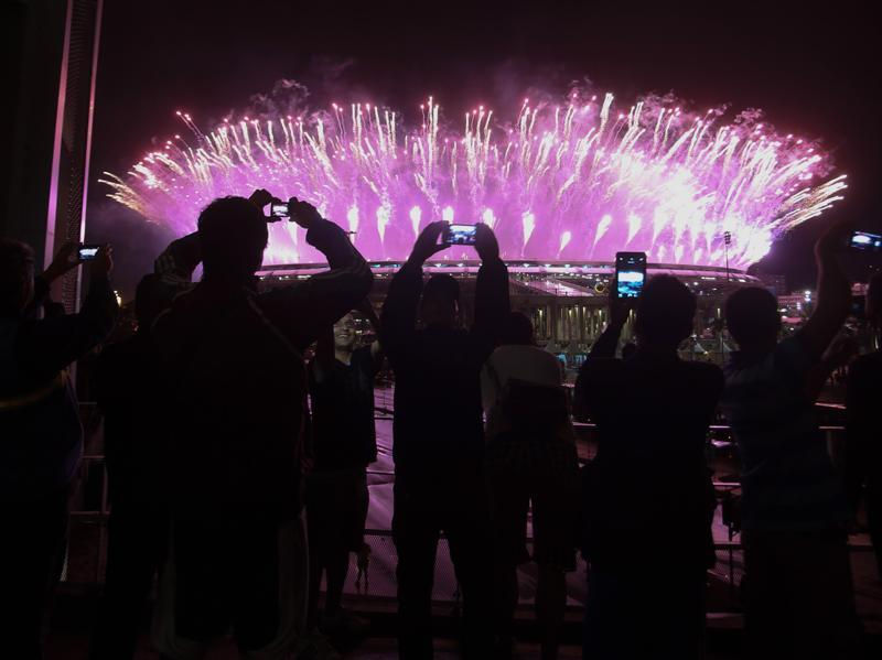 People watching from outside take photos of the fireworks display in the Maracanas stadium. (REUTERS)