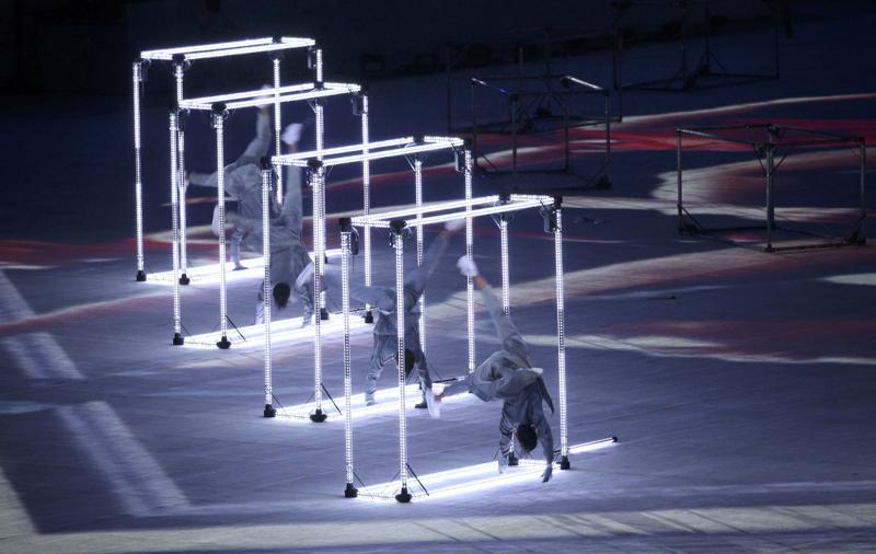 Performers execute a routine with lit trapezoidal props. (REUTERS)