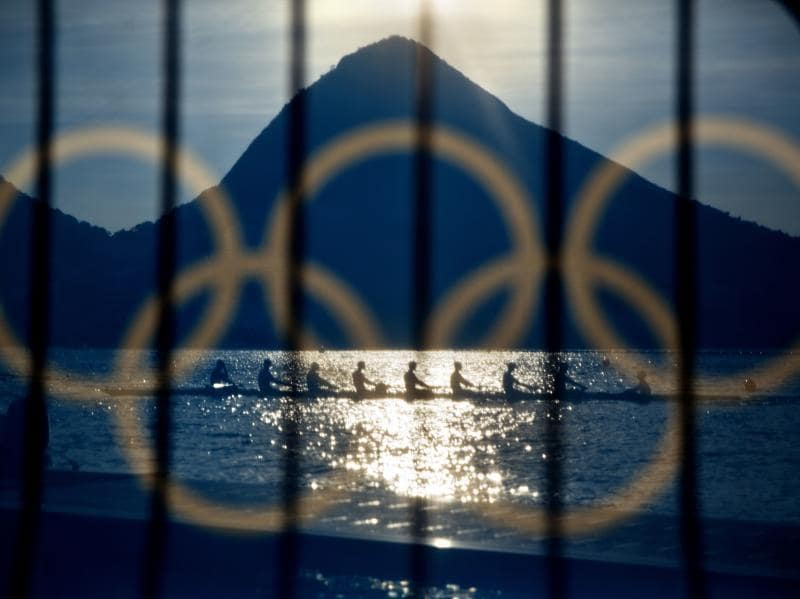 Rowers are seen through a screen decorated with the Olympic rings as they practice at the rowing venue in Lagoa at the 2016 Summer Olympics in Rio de Janeiro on August 7, 2016. (David Goldman/ AP Photo)