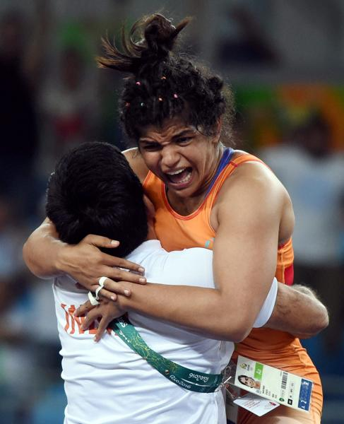 India's Sakshi Malik celebrates with her coach Kuldeep Singh after winning bronze against Kyrgyzstan's Aisuluu Tynybekova in the women's wrestling freestyle 58-kg competition on August 17. (Atul Yadav/PTI  photo)