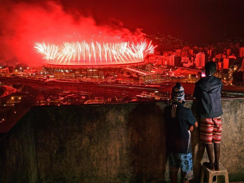 Children from Mangueira favela watch fireworks over Maracana Stadium during the Rio Games closing ceremony in Rio de Janeiro on August 21, 2016. (Carl De Souza/ AFP Photo)