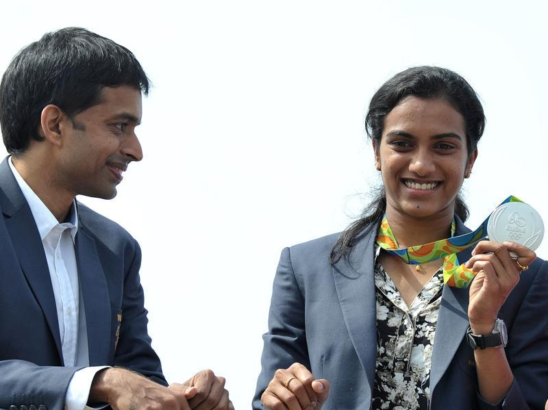 PV Sindhu (R), badminton silver medallist in Rio, and her coach Pullela Gopichand take part in a parade after her arrival in Hyderabad from Rio on August 22, 2016. (AFP)