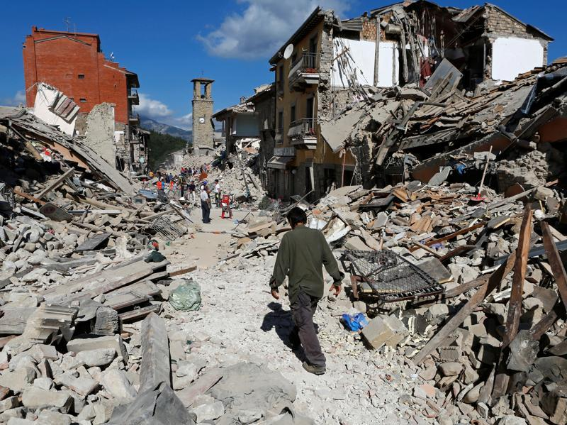 A man walks amidst rubble following an earthquake in Pescara del Tronto. (REUTERS)