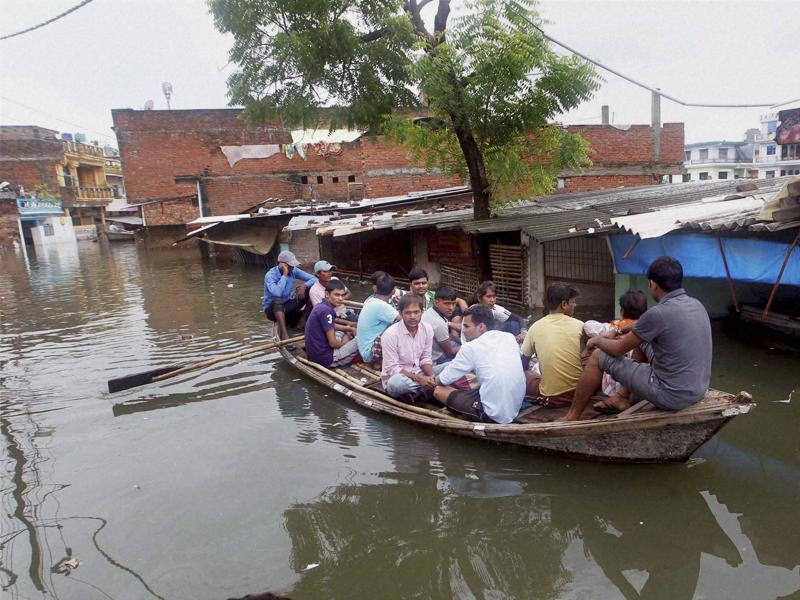 People on boat, wade through the flooded streets in Allahabad on Tuesday.  (PTI)