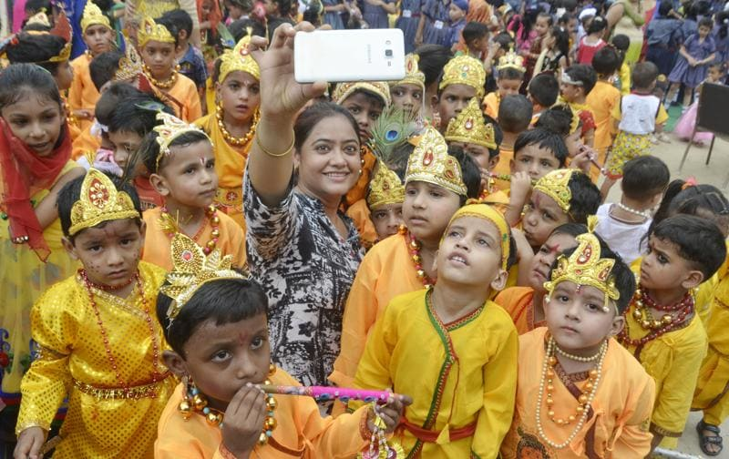 Self(ie) realisation: A teacher takes a selfie with children dressed as Lord Krishna on the eve of Janmashtami at Sun Valley Public School, Amritsar, on Wednesday. (Sameer Sehgal/HT Photo)
