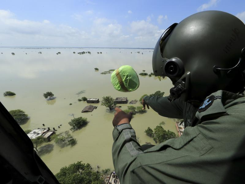 An Indian Air Force official drops relief materials to people affected by floods in Allahabad. (AP/Rajesh Kumar Singh)