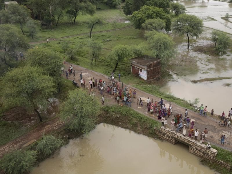 People wait for relief material being distributed by helicopter near Allahabad.  (AP/Rajesh Kumar Singh)