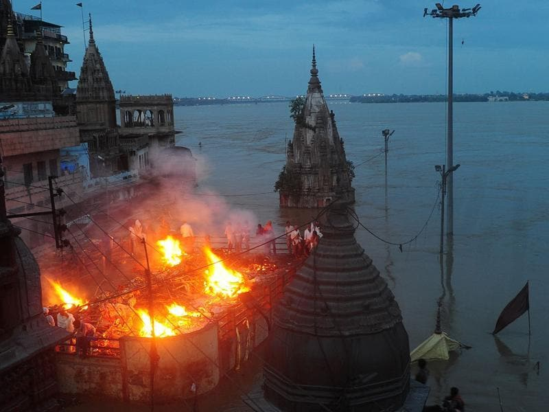 A cremation  is performed on the roof of a building overlooking Manikarnika Ghat in Varanasi on August 23, as a swollen Ganga submerged the banks of the river.  (AFP/Sanjay Kanojia)