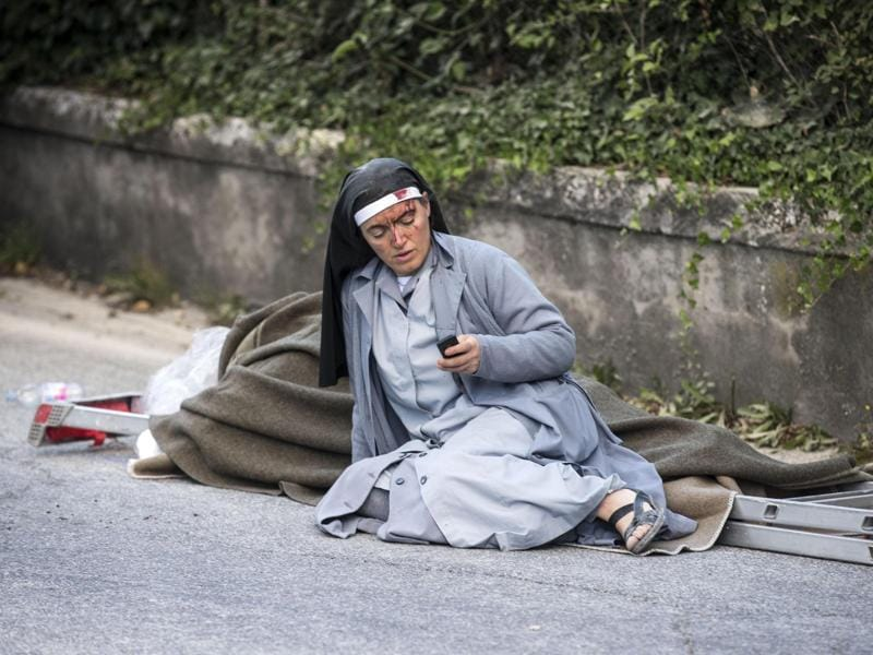 A nun checks her mobile phone as she lies near a ladder following an earthquake in Amatrice. (AP Photo)