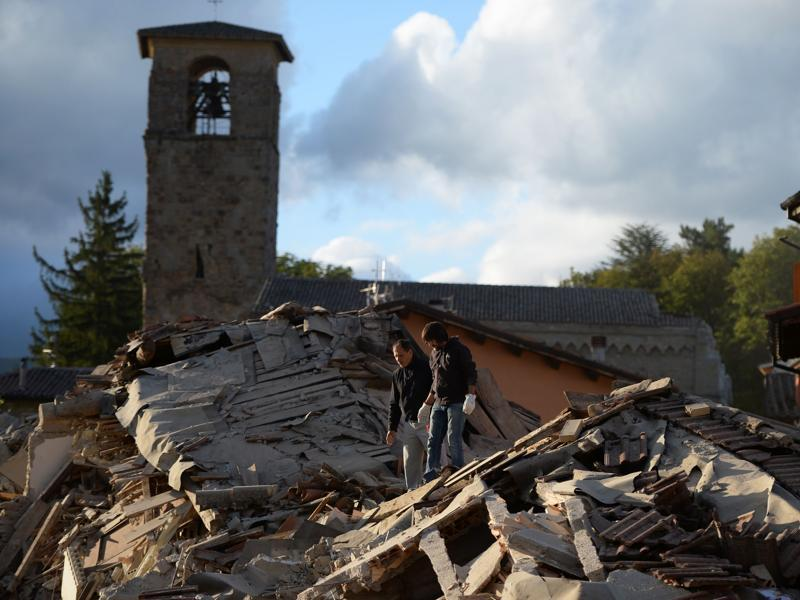 Two men walk on a damaged home after a strong earthquake hit Amatrice. The first quake struck shortly after 3.30 am (0130 GMT), according to the United States Geological Survey.  (AFP Photo)