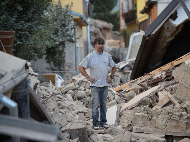 A man stands on a damaged home after a strong earthquake hit Amatrice.  Numerous buildings collapsed in small communities close to the epicentre of the quake in a remote, thinly-populated area straddling the regions of Umbria, Marche and Lazio.  (AFP Photo)
