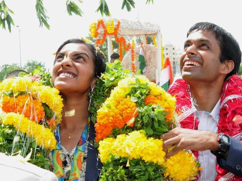 Sindhu and Gopichand acknowledge the crowd as they are welcomed with garlands. (PTI)