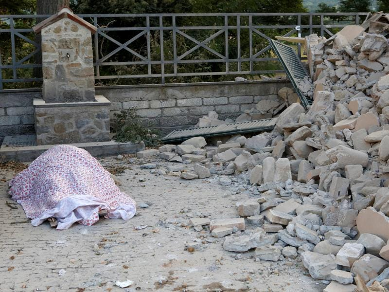 A body is covered by cloth next to rubble following a quake in Amatrice, central Italy.  (REUTERS)