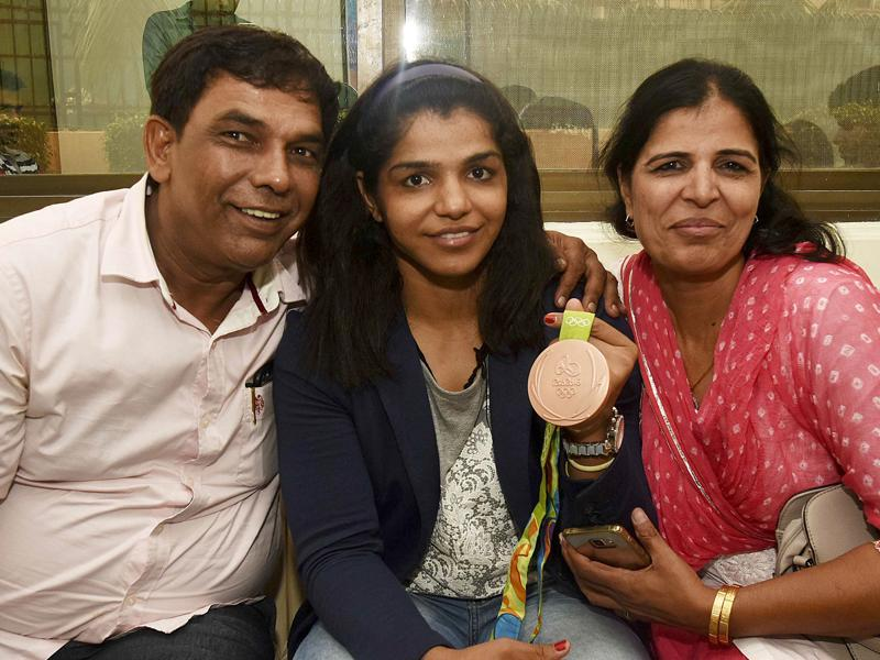 Sakshi Malik poses for a photo with her parents at Haryana State Guest House in New Delhi. (Vipin Kumar/HT PHOTO)