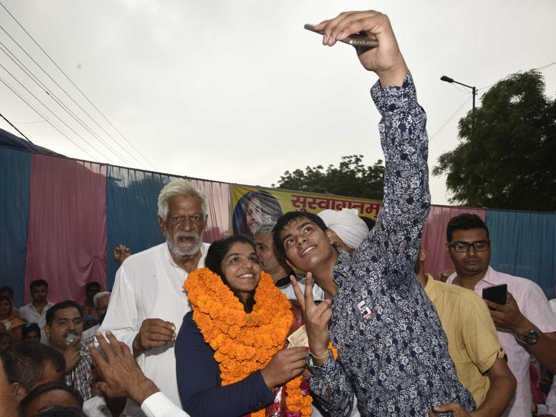Sakshi Malik takes a selfie with a fan in Tikri Border village on her way to her home town in Rohtak. (Vipin Kumar/HT PHOTO)