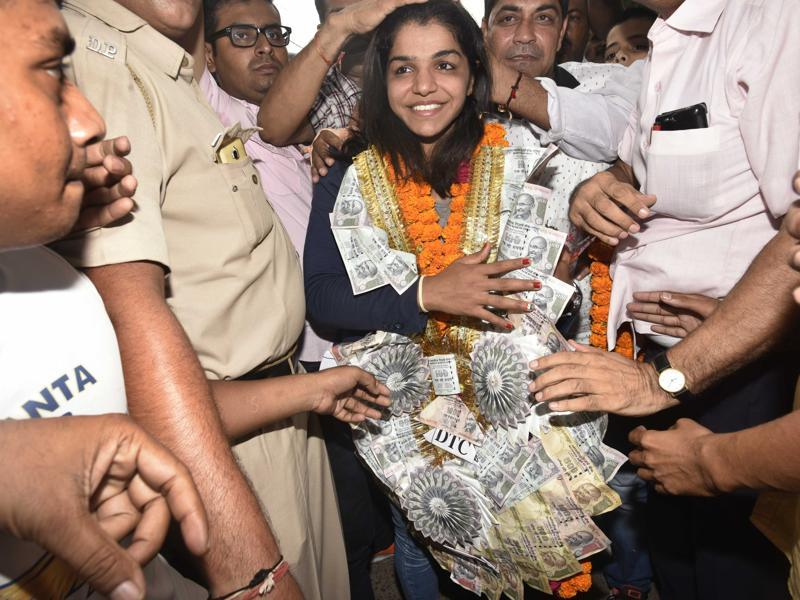 Sakshi Malik is welcome with a garland of flowers and currency notes on her arrival at Tikri Border village on her way to her home town at Rohtak. (Vipin Kumar/HT PHOTO)
