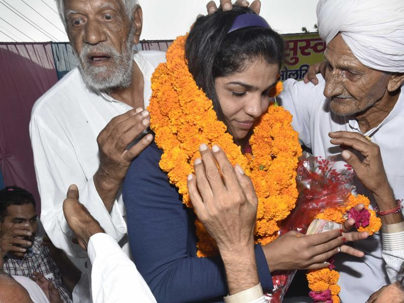 Sakshi Malik receive blessings from village elders at Tikri Border village on her way to Rohtak. (Vipin Kumar/HT PHOTO)