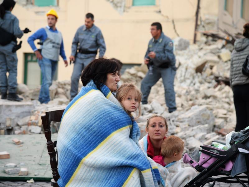 Victims sit among the rubble of a house after a strong earthquake hit Amatrice on August 24, 2016. (AFP Photo)